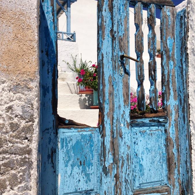 Porte bleue et géraniums roses à Pyrgos sur l'île de Santorin.